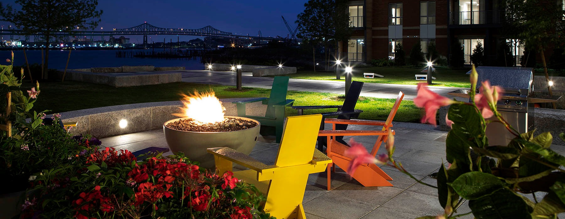 fire pit with lawn chairs at night with views of the harbor